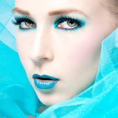 Beautiful woman with extreme colorfull make up in turquoise — Stock Photo