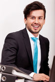 Young businessman smiling at office — Stock Photo