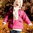Cute little child playing outdoor in autumn — Stock Photo