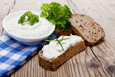 Yoghurt creamy cheese with herbs and bread — Stock Photo