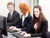 Callcenter service team talking with headset — Stock Photo