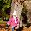 Cute littloe girl playing outdoor in autumn — Stock Photo #18624343