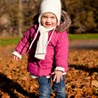 Cute littloe girl playing outdoor in autumn — Stock Photo