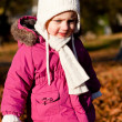 Cute littloe girl playing outdoor in autumn — Stock Photo #18624597