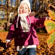 Cute littloe girl playing outdoor in autumn — Stock Photo #18625205