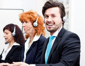 Smiling callcenter agent with headset support — Stock fotografie