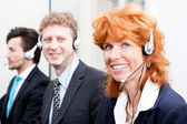 Smiling callcenter agent with headset support — Foto Stock