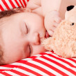 Sleeping cute little baby on red and white stripes pillow — Stock Photo