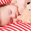 Sleeping cute little baby on red and white stripes pillow — Stock Photo #20101135