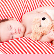 Sleeping cute little baby on red and white stripes pillow - Stock Photo