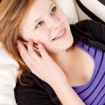 dospívající dívka Usmívá a ležel na gauči s mobilním telefonem — Stock fotografie #21245859