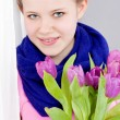 Smiling teenager girl with pink tulips bouquet - Stock Photo