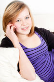 Teenager girl smiling and lying on couch with mobile phone — Stock Photo