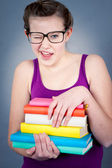 Silly smiling schoolgirl with glasses and lots of books — Stock Photo