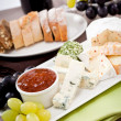 Cheese plate with grapes and wine dinner — Stock Photo #22095281