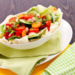 Fresh mixed colorful salad on wooden table — Stock Photo #22411811