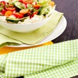 Fresh mixed colorful salad on wooden table — Stock Photo