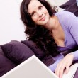 Smiling woman on couch with notebook — Stock Photo