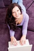 улыбается женщина на диване с ноутбуком — Стоковое фото