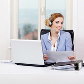 Smiling young female callcenter agent with headset — Stock Photo
