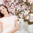 Beautiful young woman and pink magnolia — ストック写真