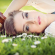 Beautiful woman lying in grass in summer — Stock Photo