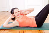 Attractive young woman doing sit ups — Stock Photo