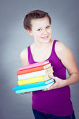 Silly smiling schoolgirl with lots of books — Stock Photo