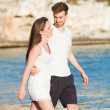 Young happy couple walking on beach sunset holiday — Stock Photo