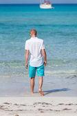 Junger Mann, Wandern am Strand im Urlaub — Stockfoto