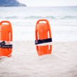 Orange red life buoy in sand on beach at the sea object — Stock Photo #27120477