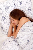 Young brunette woman lying in bed sleeping morning — Stock Photo