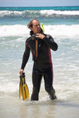 Male diver with diving suit snorkel mask fins on the beach — Stock Photo