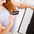 Girl sitting in bed and shopping online with credit card — Stock Photo