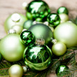 Shiny green christmas baubles closeup macro and tree  — Stockfoto