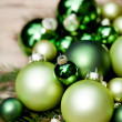 Shiny green christmas baubles closeup macro and tree — Stock Photo