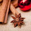 Christmas decoration cinnamon anise baubles in red — Stock Photo