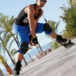 Young man with inline skates in summer outdoor — Stock Photo