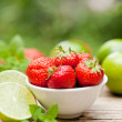 Fresh tasty sweet strawberries and green lime outdoor in summer — Stock Photo