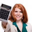 Attractive smiling redhead business woman with calculator isolated — Stockfoto