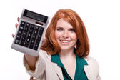 Attractive smiling redhead business woman with calculator isolated — Stock Photo