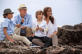 Happy family sitting on rock and watching the ocean waves — Stock Photo