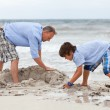 Father and sons on the beach playing in the sand — Stock Photo