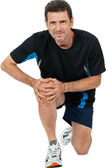 Adult attractive man in sportswear knee pain injury ache isolated — Stock Photo