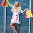 Smiling blonde woman with colorful bags on shopping tour — Stok fotoğraf
