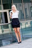 Sonrisa a atractiva rubia empresaria con smartphone — Foto de Stock