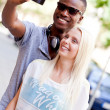 Young smiling multiracial couple taking foto by smartphone — Stock Photo #30410061