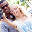 Young smiling multiracial couple taking foto by smartphone  — Stock Photo
