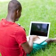 Young smiling african student sitting in grass with notebook — Stockfoto