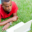 Young smiling african student sitting in grass with notebook — Stock Photo